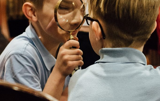 Boy looking at friend through a magnifying glass